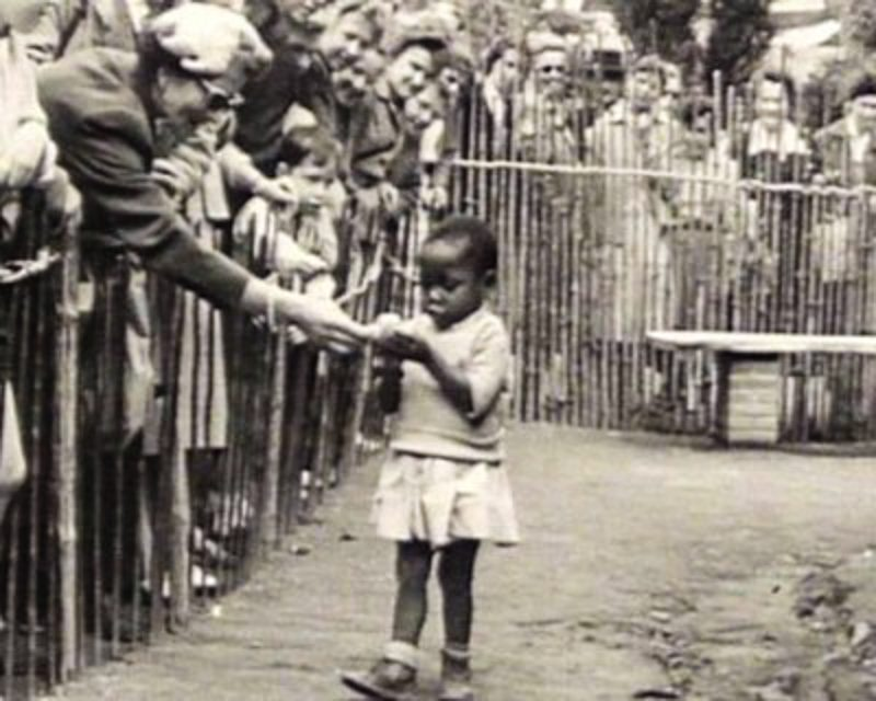 """At a """"Peoples Shows"""" in Brussels, Belgium, where a young Black girl is fed by spectators. Image: Public Domain"""