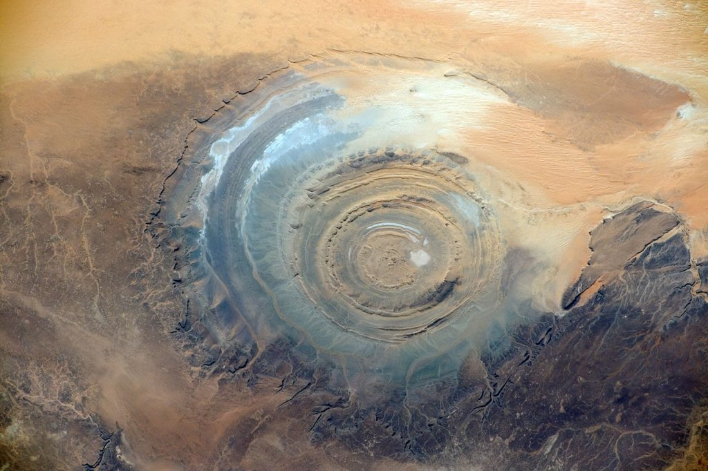 The Richat Structure, also known as the Eye of the Sahara and Guelb er Richat, is a prominent circular feature in the Sahara near Ouadane, west–central Mauritania. Image: NASA / ISS