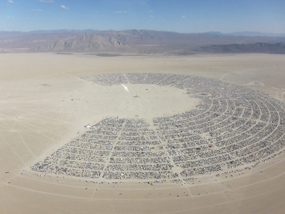 "Aerial photo of Black Rock City showing the familiar ""C"" pattern 2010. Source: Wikipedia"