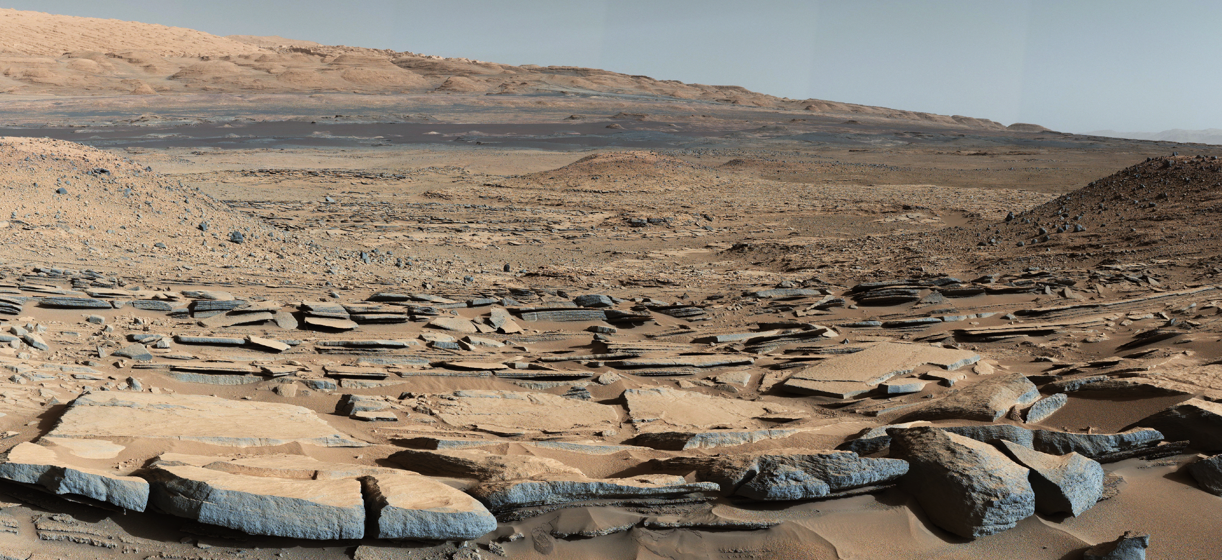 """A view from the """"Kimberley"""" formation on Mars taken by NASA's Curiosity rover. The strata in the foreground dip towards the base of Mount Sharp, indicating flow of water toward a basin that existed before the larger bulk of the mountain formed. Credits: NASA"""